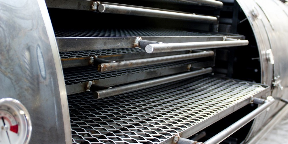 stainless steel cooking grills inside a custom built bbq smoker